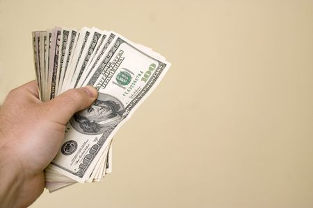 A handful of cash isolated over a gold background. Stock Photo - 3223130