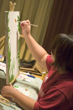 A young woman doing working with oil paints on canvas. photo