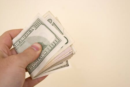 moola: A hand holding a big wod of cash isolated over a gold background.