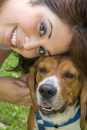A pretty girl posing with her beagle dog.  Shallow depth of field. photo