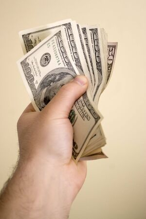 moola: A handful of cash isolated over a solid background.