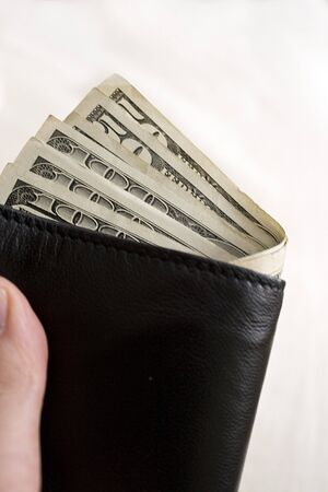 moola: A hand holding a wallet full of cash isolated over a gold background. Stock Photo
