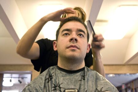 barbershop: A young man getting his hair cut by a hairdresser at the salon Stock Photo