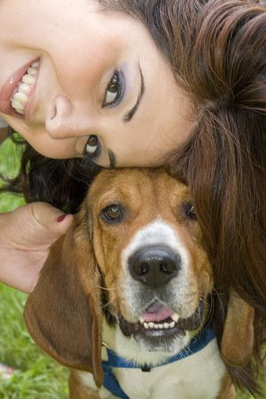 seem: A pretty girl posing with her beagle dog - they both seem to be smiling.