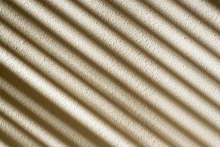 diagonal lines: The light shining in through the blinds, creating an interesting pattern on the textured wall. Stock Photo
