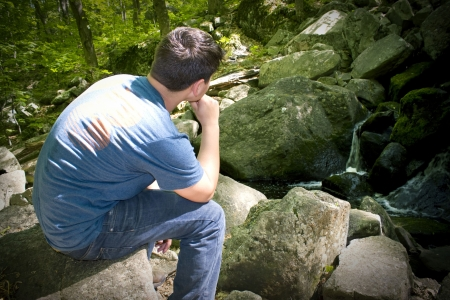 deep thought: A young man in deep thought while sitting on some rocks near a beautiful waterfall.