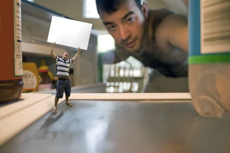 overeat: A miniature man holding up a blank sign inside the refrigerator.  Possible text on the sign could be WHATS FOR DINNER or WE NEED FOOD.  Use your imagination!  Shallow depth of field. Stock Photo