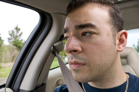 as: This young man looks bored and stares out the window while riding as a passenger on a long road trip. Stock Photo