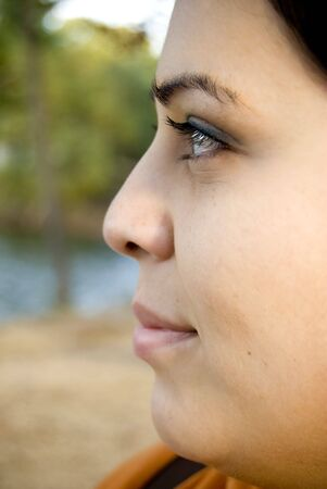 A side profile closeup of a young Spanish womans face. photo