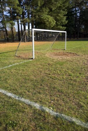 A soccer goal sits at the end empty field at the park. photo