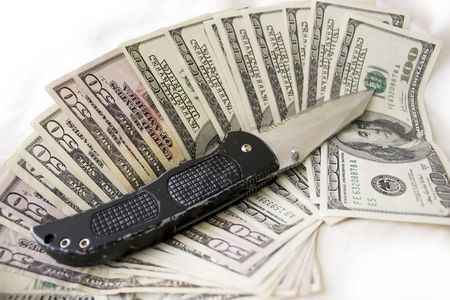 A knife and some fanned out cash laying on a bed.  This works for all sorts of illegal activities such as prostitution, drug dealing, and gang activity. photo