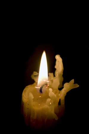 melts: A creepy old candlestick burns on as it melts down little by little. Stock Photo