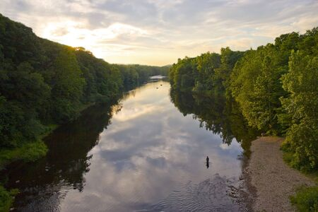 outdoorsman: A glorious view of the Farmington River around dusk.  A patient fly fisherman is seen enjoying his hobby.