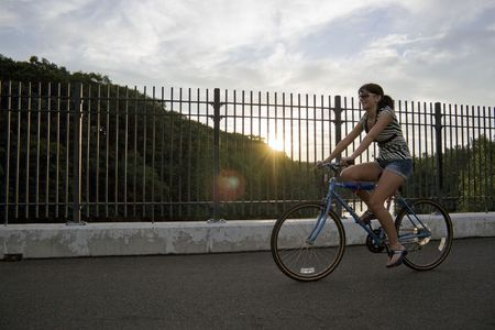 across: A young woman riding a bicycle across the bridge. Stock Photo
