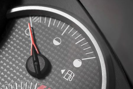 gage: Closeup of a gas gage from a car.  It has selective color and the needle is pointing to empty.
