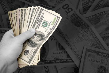 moola: A handful of cash.  The money has selective color, and the rest of the image is in black and white - plenty of copy space. Stock Photo
