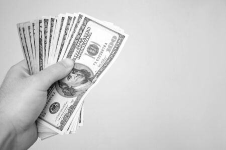 moola: A handful of cash isolated over a solid background in black and white.