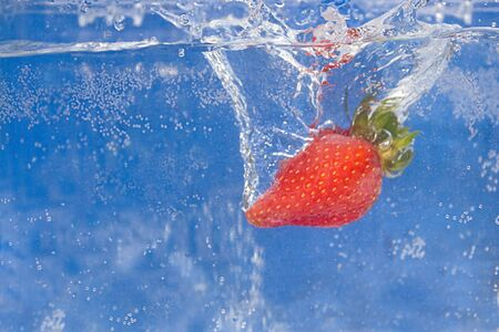 A juicy red strawberry plunging into some water. Stock Photo