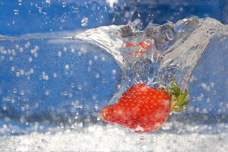 A juicy red strawberry plunging into some water. photo