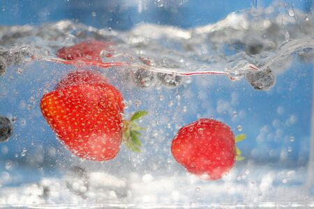 Some juicy red strawberries plunging into crystal clear water. Stock Photo