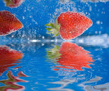 some: Some juicy red strawberries plunging into some water with reflections.