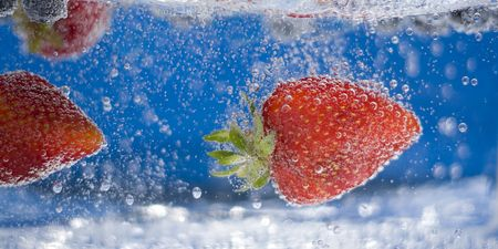 Juicy red strawberries and blueberries plunging into some water. Stock Photo - 3551682