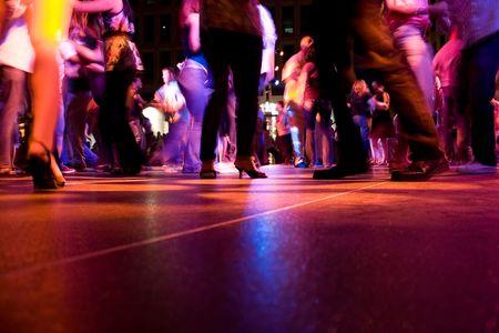 カラフルなライトの下で踊る人々 とダンスフロアの低ショット 写真素材