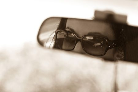 sunglasses reflection: The face of a young woman driving as seen in the rear view mirror.