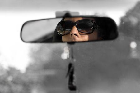 sunglasses reflection: The face of a young woman driving as seen in the rear view mirror in isolated color.