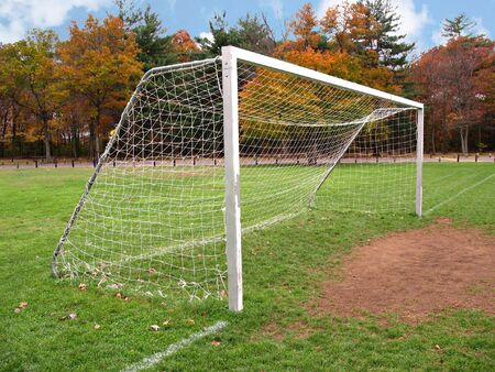 A soccer goal sits at the end empty field at the park.