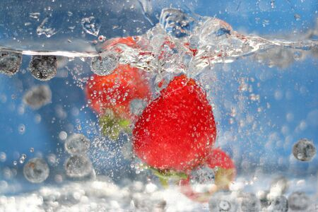 Juicy red strawberries and blueberries plunging into some sparkling water.  Shallow depth of field. Stock Photo