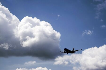 A silhouette of a commercial passenger plane over a blue sky in its descent to land. Banco de Imagens