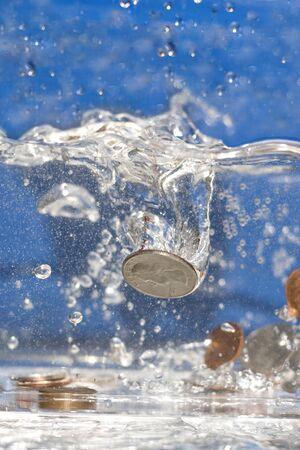 desague: Un pu�ado de monedas cayendo en una piscina de agua.  Foto de archivo