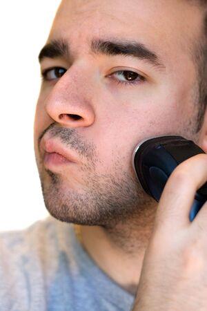hombre afeitandose: A closeup de un joven afeitado la barba con una rasuradora el�ctrica.  Foto de archivo