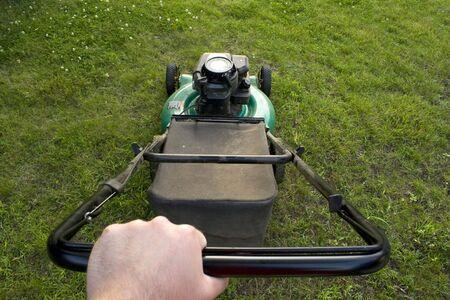 hombre empujando: El interesante punto de vista de un hombre empujando una cortadora de c�sped.
