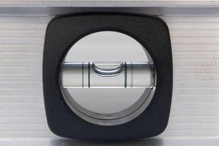 bubble level: A closeup of a carpenters bubble level with a brushed aluminum finish.
