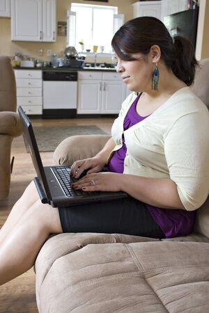 Un polo di attrazione più giovani dimensioni modello di lavoro per il suo computer portatile a casa. Molte donne scelgono di lavorare da casa più di una normale situazione aziendale. Archivio Fotografico - 3670417