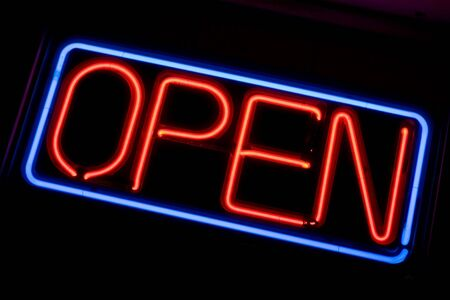 close p: A neon OPEN sign glowing red in the window of a restaurant.