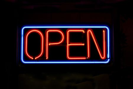 shop sign: A neon OPEN sign glowing red in the window of a restaurant.