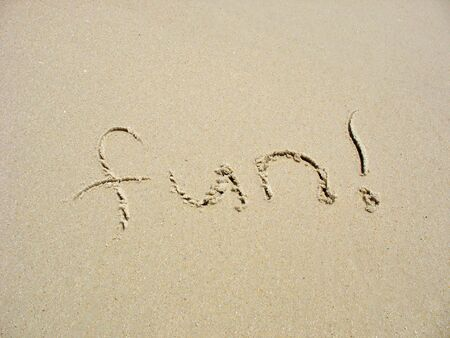 The word FUN! is written in the sand on the beach. photo
