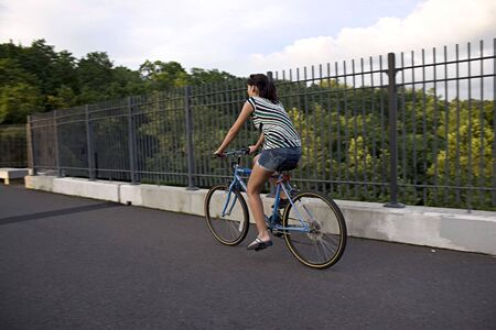 A young woman riding a bicycle across the bridge. photo