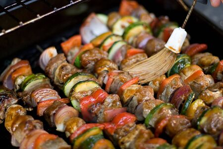 Beef shish kebabs on skewers, cooking on the grill.