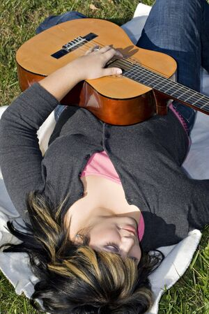 blonde streaks: A young hispanic woman playing a guitar while laying on a blanket in the green grass.  Her hair is highlighted with blonde streaks.