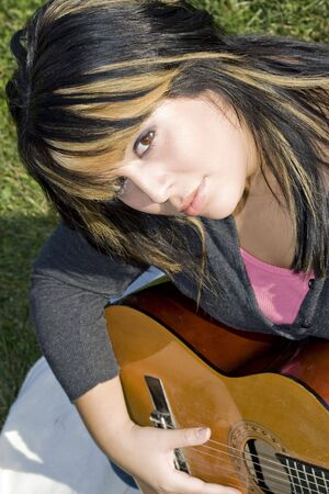 blonde streaks: A young hispanic woman playing a guitar while sitting on a blanket in the green grass.  Her hair is highlighted with blonde streaks. Stock Photo