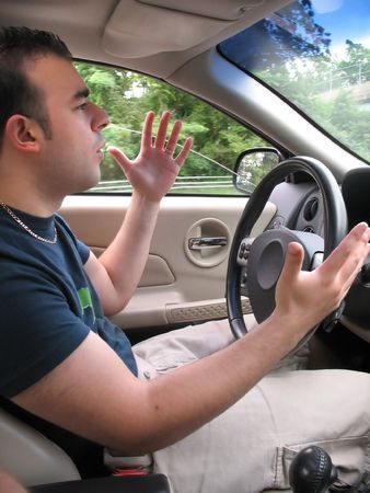 A young man seems to be experiencing some road rage while driving. photo
