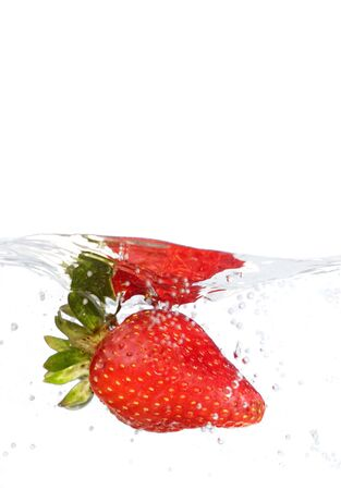 A juicy red strawberry plunging into some water. Shallow depth of field. Stockfoto
