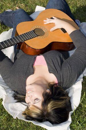 highlighted hair: Una giovane donna ispanica giocando una chitarra mentre posa su una coperta nel verde erba. I suoi capelli biondi � evidenziato con striature.