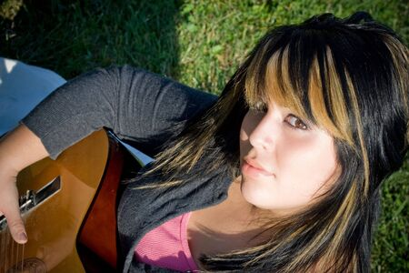 highlighted hair: A young hispanic woman playing a guitar while laying on a blanket in the green grass.  Her hair is highlighted with blonde streaks.