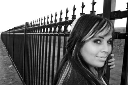 highlighted hair: A young girl with highlighted hair posing by a fence - black and white. Stock Photo