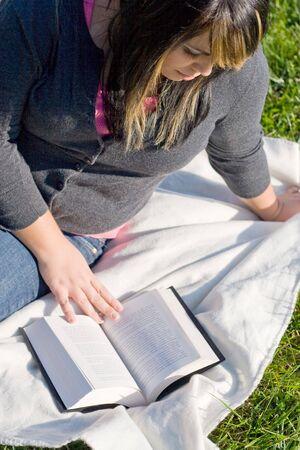 highlighted hair: Una giovane donna con i capelli in evidenza la lettura di un libro o facendo a casa nel campus. Archivio Fotografico